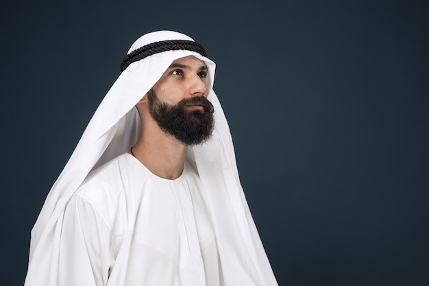 Half-length portrait of arabian saudi businessman on dark blue wall. young male model standing and looks thoughtful. concept of business, finance, facial expression, human emotions.