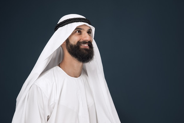 Half-length portrait of arabian saudi businessman on dark blue wall. young male model standing and smiling. concept of business, finance, facial expression, human emotions.