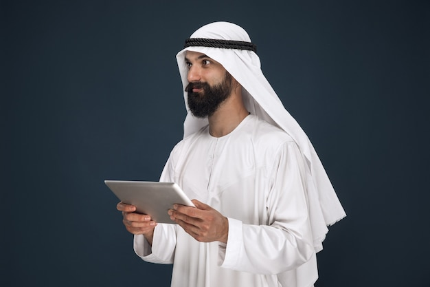 Half-length portrait of arabian saudi businessman on dark blue wall. young male model using tablet or gadget. concept of business, finance, facial expression, human emotions, technologies.