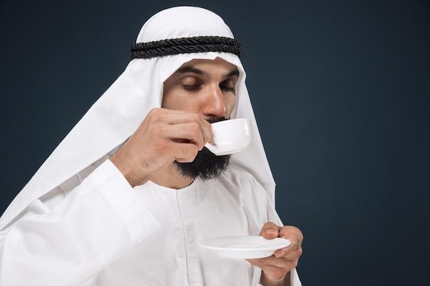 Ritratto a mezzo busto dell'uomo d'affari arabo saudita su blu scuro