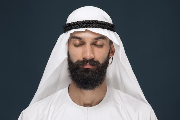 Half-length portrait of arabian saudi businessman on dark blue