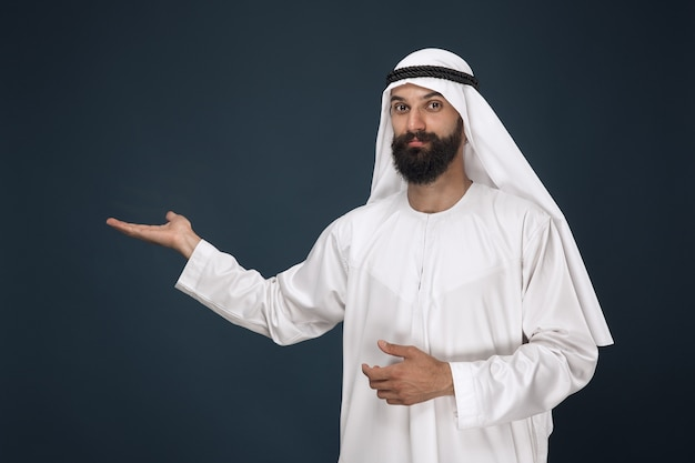 Half-length portrait of arabian saudi man on dark blue  space. young male model smiling and pointing