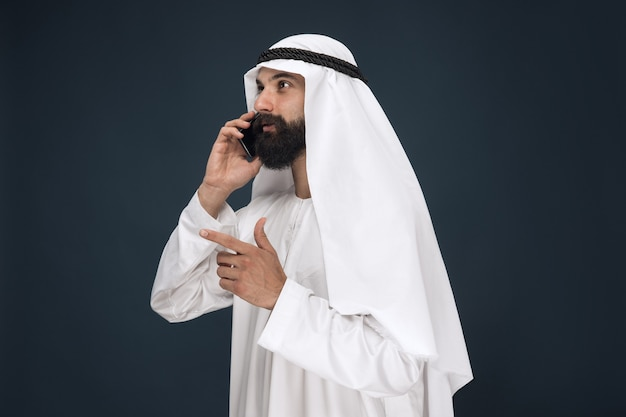 Half-length portrait of arabian saudi man on dark blue studio wall. male model using smartphone, making a call. concept of business, finance, facial expression, human emotions, technologies.
