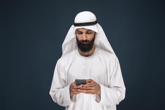 Ritratto a mezzo busto dell'uomo arabo saudita su studio blu scuro