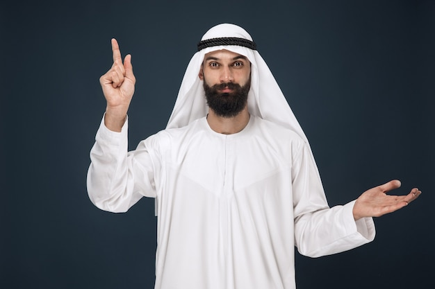 Half-length portrait of arabian saudi man on dark blue wall. young male model smiling and pointing. concept of business, finance, facial expression, human emotions, technologies.