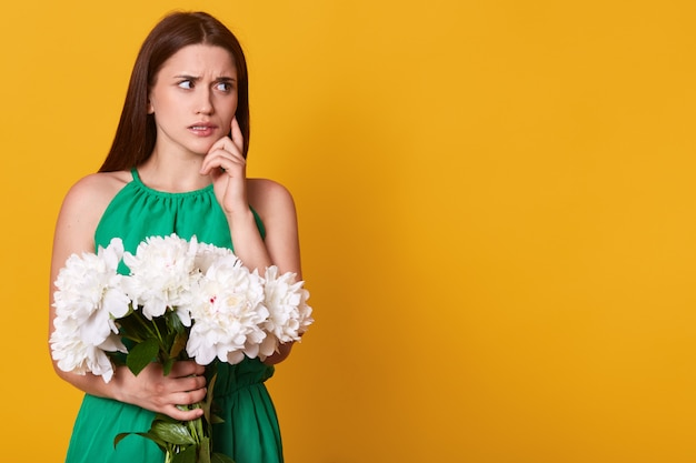 Half length portrait of attractive brunette woman in green sundress holding bouquet of white peonies on yellow, looking pensivly aside, keeps finger on cheek, copy space for advertisment.