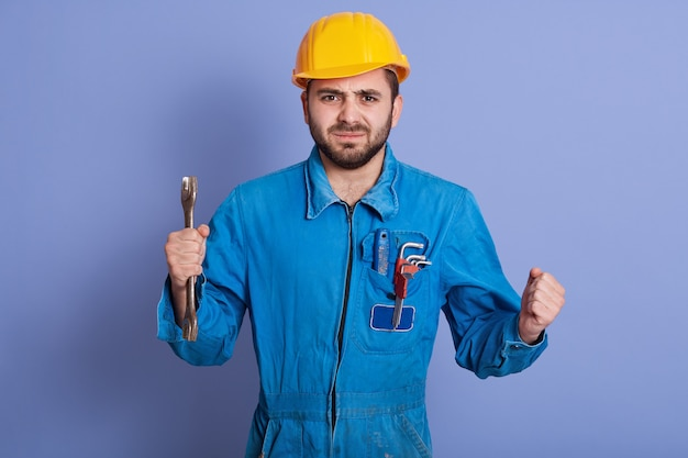 Half length portrait of confident worker holding wrench in hand, being very angry, clenching fists with anger, has serious facial expression, stands in uniform and helmet isolated over blue