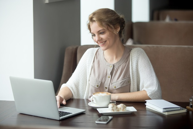 Half-length portrait of happy woman using laptop in cafe
