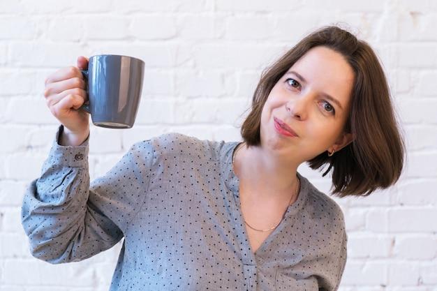 흰색 벽돌 벽의 배경에 대해 손에 커피 한 잔을 들고 있는 젊은 갈색 머리 여성의 반장 초상화. 여자는 미소를 지으며 손에 세라믹 회색 머그를 들고 있습니다.