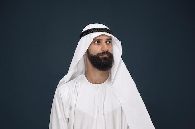 진한 파란색 공간에 아라비아 사우디 사업가의 길이 초상화. 젊은 남성 모델 입석 및 사려 깊은 보인다