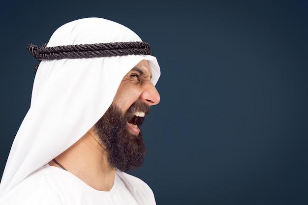 Поясной портрет арабского саудовского бизнесмена на синем фоне студии. молодой мужской модель позирует и кричит, выглядит сердитым. понятие бизнеса, финансов, выражения лица, человеческих эмоций.