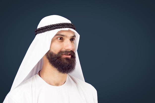Поясной портрет арабского саудовского бизнесмена на синем фоне студии. молодой мужской модели позирует и улыбается, выглядит счастливым. понятие бизнеса, финансов, выражения лица, человеческих эмоций.