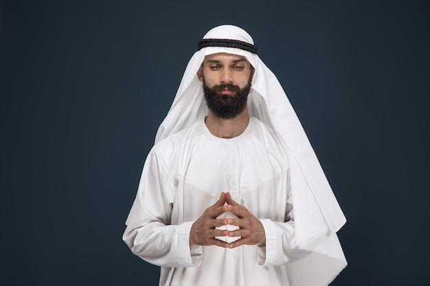ダークブルーのスタジオの背景にアラビアのサウジアラビアの実業家の半分の長さの肖像画。祈って思慮深く見える若い男性モデル。ビジネス、金融、顔の表情、人間の感情の概念。