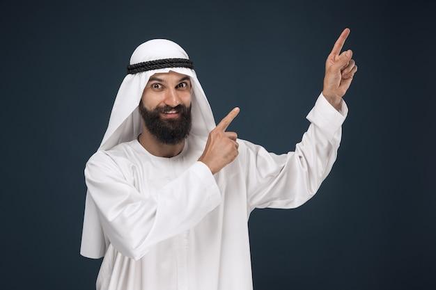 진한 파란색 스튜디오 배경에 아라비아 사우디 사업가의 길이 초상화. 웃 고 가리키는 또는 선택 젊은 남성 모델. 비즈니스, 금융, 표정, 인간 감정의 개념.