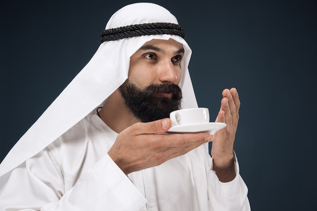 진한 파란색 스튜디오 배경에 아라비아 사우디 사업가의 길이 초상화. 서 커피 또는 차를 마시는 젊은 남성 모델. 비즈니스, 금융, 표정, 인간 감정의 개념.