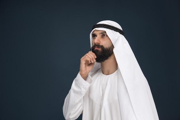 ダークブルーのスタジオの背景にアラビアのサウジアラビアの実業家の半分の長さの肖像画。若い男性モデルが立っていて、思慮深く見えます。ビジネス、金融、顔の表情、人間の感情の概念。