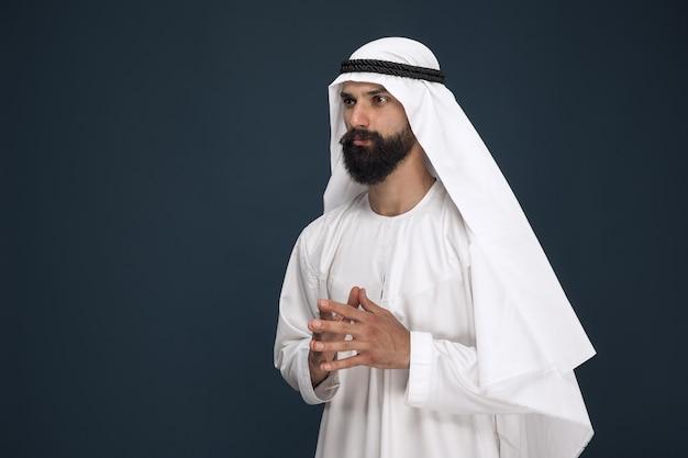 진한 파란색 스튜디오 배경에 아라비아 사우디 사업가의 길이 초상화. 젊은 남성 모델 서 있고 사려 깊은 보인다. 비즈니스, 금융, 표정, 인간 감정의 개념.