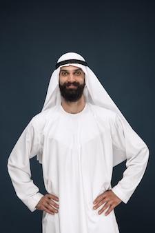 ダークブルーのスタジオの背景にアラビアのサウジアラビアの実業家の半分の長さの肖像画。立って笑っている若い男性モデル。ビジネス、金融、顔の表情、人間の感情の概念。