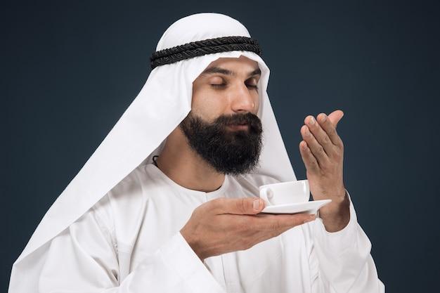 ダークブルーのスタジオでアラビアのサウジアラビアの実業家の半身像