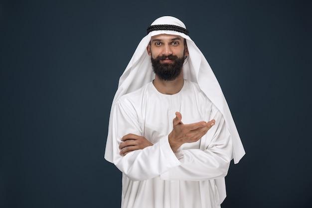 紺色の壁にアラビアのサウジアラビアの実業家の半身像。若い男性モデルの笑顔とポインティング。ビジネス、金融、表情、人間の感情の概念。