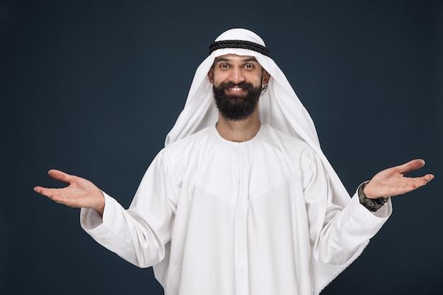 紺色の壁にアラビアのサウジアラビアの実業家の半身像。笑顔の若い男性モデル、招待のジェスチャーを示しています。ビジネス、金融、表情、人間の感情の概念。