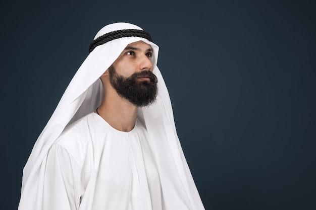 紺色の壁にアラビアのサウジアラビアの実業家の半身像。若い男性モデルが立っていて、思慮深く見えます。ビジネス、金融、表情、人間の感情の概念。