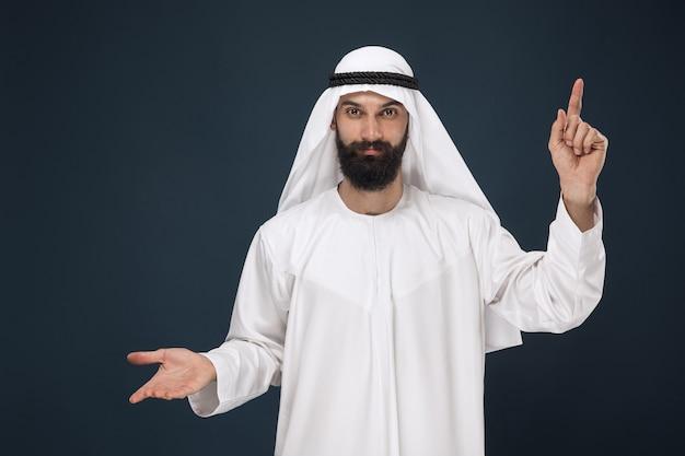 ダークブルーのスタジオの背景にアラビアのサウジアラビアの男の半分の長さの肖像画。若い男性モデルの笑顔とポインティング。ビジネス、金融、顔の表情、人間の感情、技術の概念。