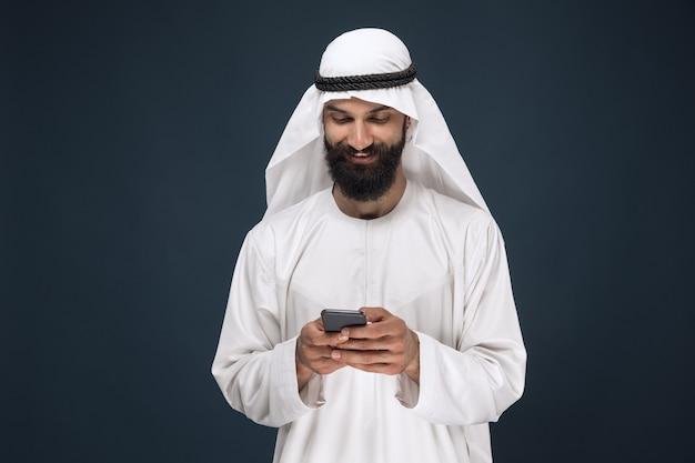 ダークブルーのスタジオの背景にアラビアのサウジアラビアの男の半分の長さの肖像画。スマートフォンを使用して、チャット、若い男性モデル。ビジネス、金融、顔の表情、人間の感情、技術の概念。
