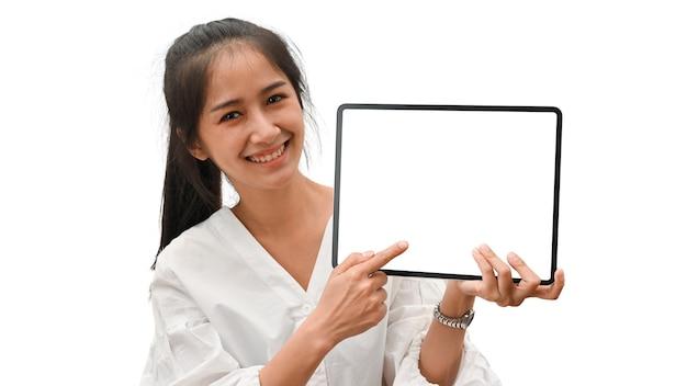モックアップ画面でデジタルタブレットを提示する女性の半分の長さの肖像画