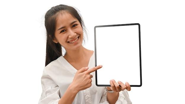 白い背景で隔離のモックアップ画面とデジタルタブレットを示す女性の半分の長さの肖像画