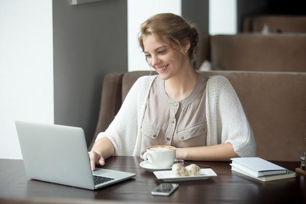 Полудлительный портрет счастливой женщины, используя ноутбук в кафе