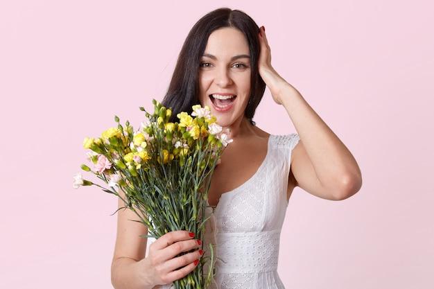 Портрет половинной длины симпатичной брюнетки, держащей букет цветов, смеясь, глядя прямо в камеру, держит руку на голове