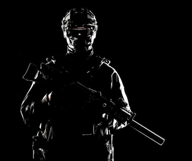 Поясной портрет солдата спецназа, армейского коммандос, тактической группы полиции или бойца спецназа со спрятанным за маской и очками лицом, вооруженной штурмовой винтовкой с глушителем, сдержанная студийная съемка