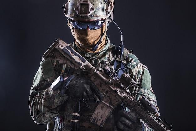 武器とフィールドの制服を着た特殊部隊の兵士の半分の長さの肖像画、黒の肖像画