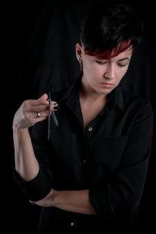 ヴィンテージストレートかみそりを保持している黒の若い大人の理髪店の女性の半分の長さの肖像画