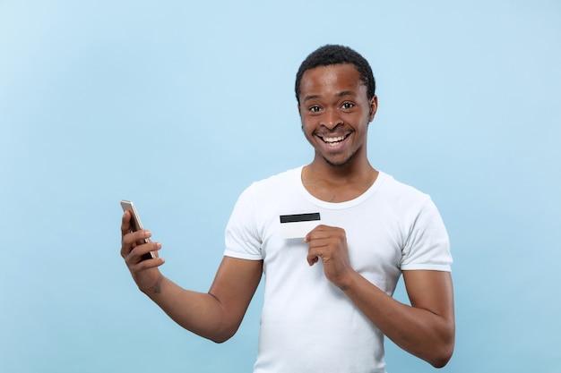 青い背景にカードとスマートフォンを保持している白いシャツを着た若いアフリカ系アメリカ人の男の半分の長さの肖像画。人間の感情、顔の表情、広告、販売、金融、オンライン決済の概念。
