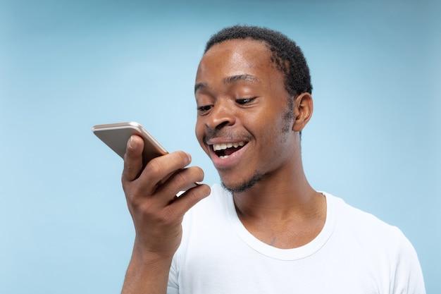 青い背景に白いシャツを着た若いアフリカ系アメリカ人の男の半分の長さの肖像画。人間の感情、表情、広告、販売コンセプト。スマートフォンを持って、話したり、音声メッセージを録音したりします。
