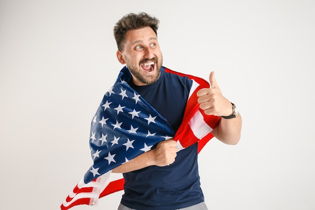 白いスタジオで隔離の米国の旗を持つ若い男の半分の長さの肖像画。