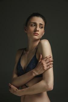 어두운 스튜디오 벽에 속옷에 젊은 슬픈 여자의 절반 길이 초상화
