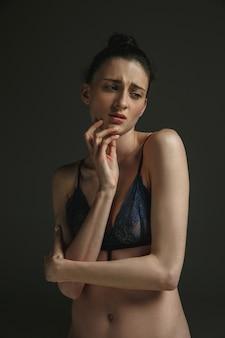 暗い壁に下着を着た若い悲しい女性の半身像。悲しみ、うつ病、中毒。人間の感情、フェミニズム、女性の問題と権利、メンタルヘルスの概念。