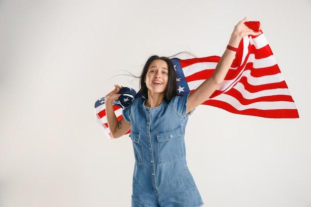 白いスタジオで隔離の米国の旗を持つ若い女性の半分の長さの肖像画。