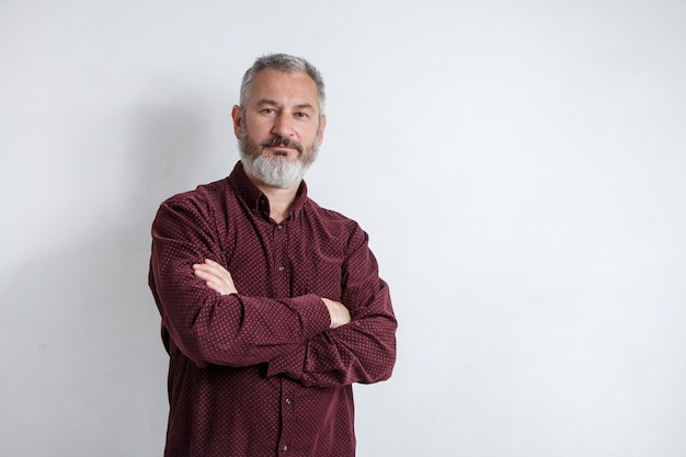 Half-length portrait of a serious gray-haired bearded man in a burgundy shirt on a white background