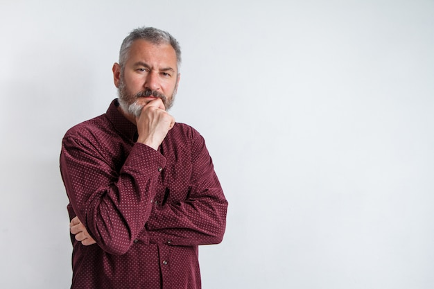 Half-length portrait of a serious gray-haired bearded man in a burgundy shirt