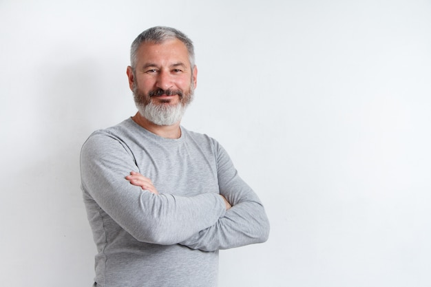 Half-length portrait of a serious gray-haired bearded man in a gray t-shirt