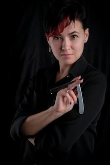 Half-length portrait of young adult barber woman on black background holding vintage straight razor, modern barber girl concept