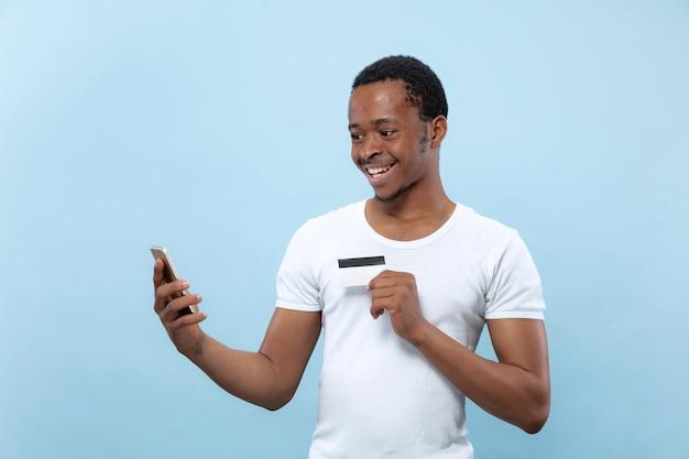 Ritratto a mezzo busto di giovane uomo afro-americano in camicia bianca che tiene una carta e smartphone su spazio blu