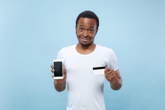 Ritratto a mezzo busto di giovane uomo afroamericano in camicia bianca che tiene una carta e smartphone su spazio blu