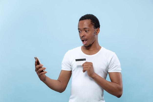 Half-length portrait of young african-american man in white shirt holding a card and smartphone on blue wall. human emotions, facial expression, ad, sales, finance, online payments concept.