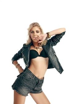 Ritratto a mezzo busto di giovane bella donna con corpo perfetto e pelle ben tenuta, indossa reggiseno e giacca di pelle