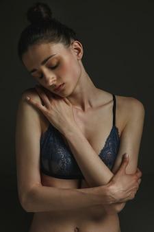 Ritratto a mezzo busto di giovane donna triste in biancheria intima sulla parete scura dello studio